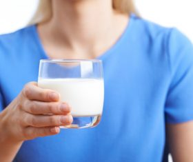Hand holding a glass of milk Stock Photo 01