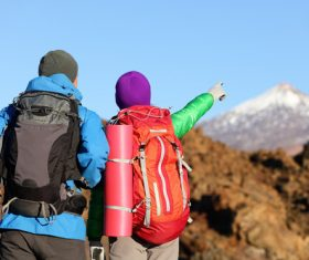 Hiking mountaineer pointing to the distant snowy mountains Stock Photo