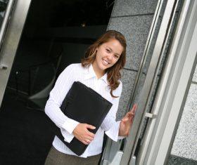 Holding black leather bag girl opening door Stock Photo