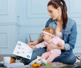 Housewife holding child looking at chart Stock Photo 01