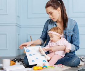 Housewife holding child looking at chart Stock Photo 02