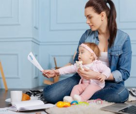 Housewife holding child looking at chart Stock Photo 03