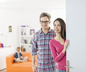 Husband and wife open the door to welcome visitors Stock Photo
