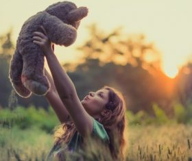 Joyful woman with teddy bear under sunlight Stock Photo