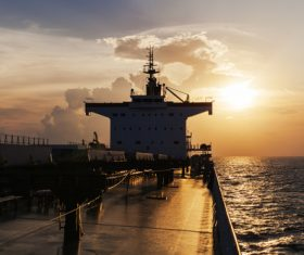 Large freighter driving in the sea in the sunset Stock Photo