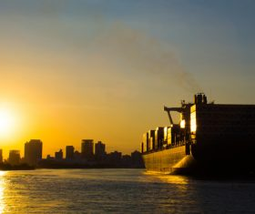 Large freighter moored in the dock at sunset Stock Photo