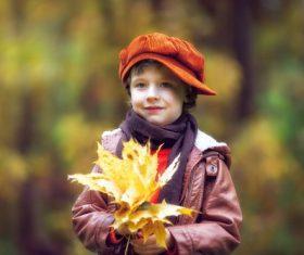 Little boy holding dead leaves Stock Photo