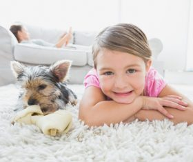 Little girl and pet dog lying on the carpet Stock Photo