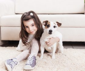 Little girl and pet dog sitting on the carpet Stock Photo