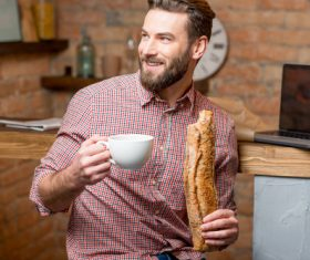 Man drinking coffee and eating bread Stock Photo