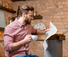 Man drinking coffee and reading newspaper Stock Photo 01