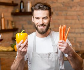 Man holding colorful peppers and carrots Stock Photo