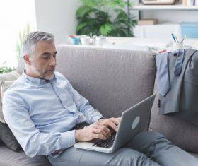 Man leaning on the couch using laptop Stock Photo
