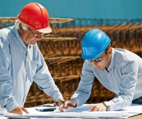 Man looking at drawings at construction site Stock Photo