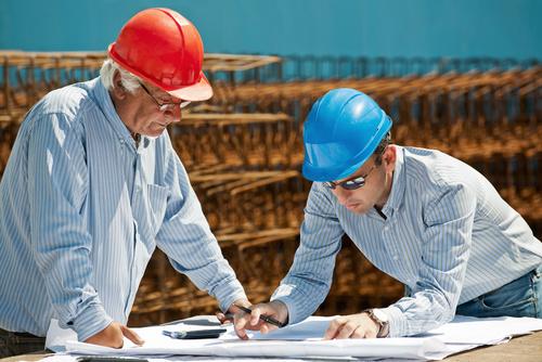 Man looking at drawings at construction site Stock Photo