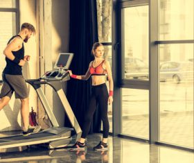 Man on treadmill and woman standing next to Stock Photo