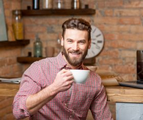 Man sitting at home drinking coffee Stock Photo