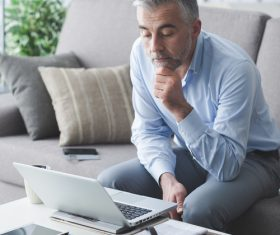 Man sitting on the couch looking at computer data Stock Photo