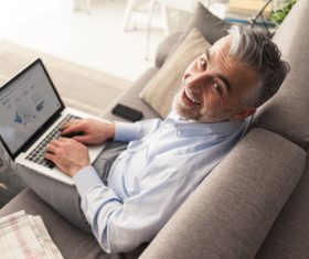 Man sitting on the couch surfing the internet Stock Photo
