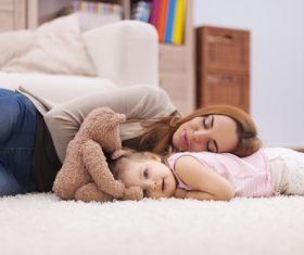 Mother and daughter lying on the carpet Stock Photo