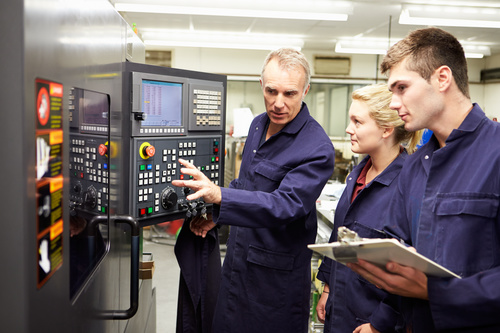 Old workers explain the control panel to young workers Stock Photo