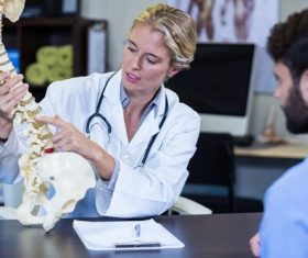 Orthopedic female doctor tells the patient about spinal disease Stock Photo 01