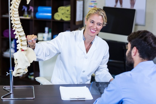 Orthopedic female doctor tells the patient about spinal disease Stock Photo 02