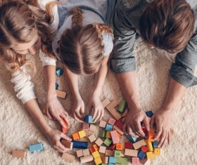 Parents build blocks with their daughter on the carpet Stock Photo