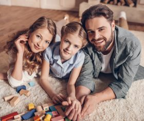 Parents play with their daughter on the carpet Stock Photo
