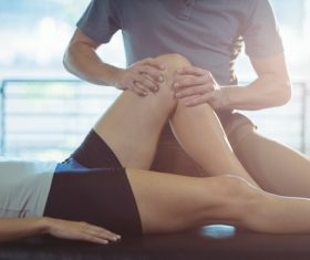 Physiotherapist giving knee therapy to a woman Stock Photo 01