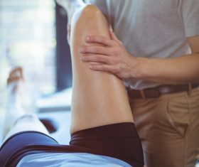 Physiotherapist giving knee therapy to a woman Stock Photo 02