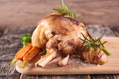 Roasted leg of lamb and carrot on cutting board Stock Photo