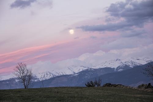 Round sun above snowy mountain Stock Photo