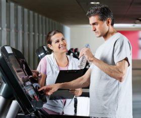 Smiling female coach guiding elderly man to exercise on treadmill Stock Photo