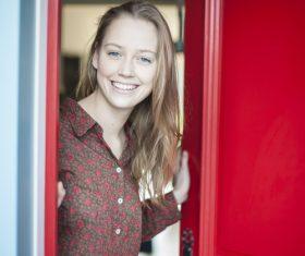 Smiling girl opening the door Stock Photo