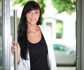 Smiling woman opening door Stock Photo