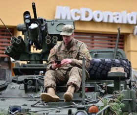 Soldiers in armored cars look at mobile phones Stock Photo