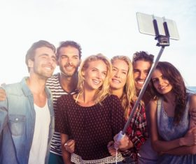 Standing on the beach young friends selfie Stock Photo