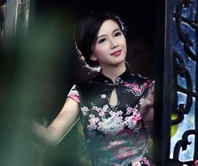 Stock Photo Asian cheongsam girl standing in front of the window