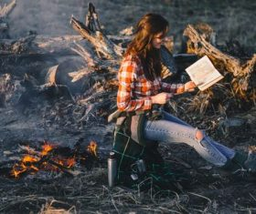 Stock Photo Girl looking at the map by the campfire