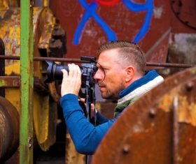 Stock Photo Male photographer shooting abandoned factory building