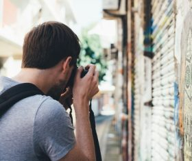 Stock Photo Man with camera taking street scene