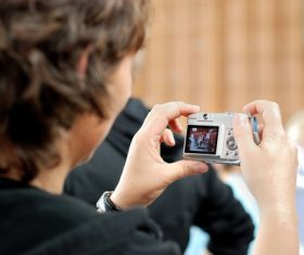 Stock Photo Mother uses digital camera to shoot childrens sports