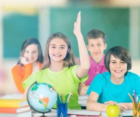 Students raise their hands in class Stock Photo