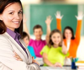 Teachers and students raising their hands in class Stock Photo