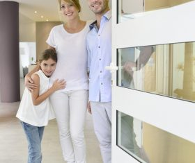 The family opens the door to welcome visitors Stock Photo