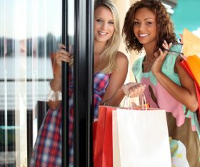 Two girls holding shopping bags opening door Stock Photo