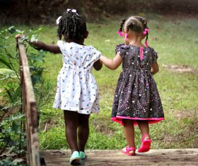 Two little girls hand in hand over wooden bridge Stock Photo