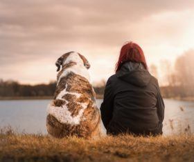 Woman and pet dog sitting by the river Stock Photo