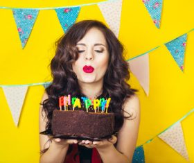 Woman blowing birthday candles Stock Photo